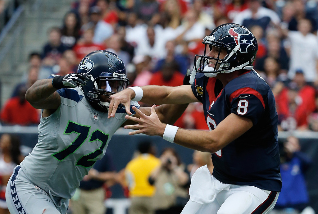 . HOUSTON, TX - SEPTEMBER 29:  Matt Schaub #8 of the Houston Texans passes as Michael Bennett #72 of the Seattle Seahawks defends at Reliant Stadium on September 29, 2013 in Houston, Texas.  (Photo by Scott Halleran/Getty Images)