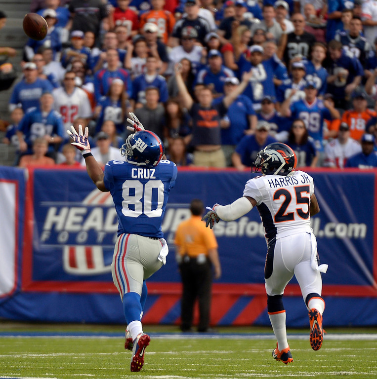 . Wide receiver Victor Cruz (80) of the New York Giants catches a long pass from quarterback Eli Manning (10) of the New York Giants as cornerback Chris Harris (25) of the Denver Broncos defends on the play during the first quarter September 15, 2013 MetLIFE Stadium. (Photo by John Leyba/The Denver Post)