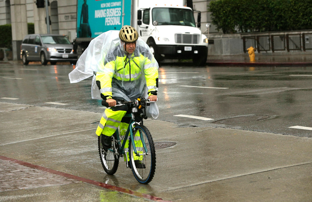 . A man dressed in rain coat rides his bike in the rain in downtown Los Angeles on Friday, Feb. 17, 2017. A powerful Pacific storm blew into southern and central California on Friday with wind-driven heavy rains, triggering calls for evacuations, causing damage and injury as trees toppled and disrupting travel and outdoor events. (AP Photo/Nick Ut)