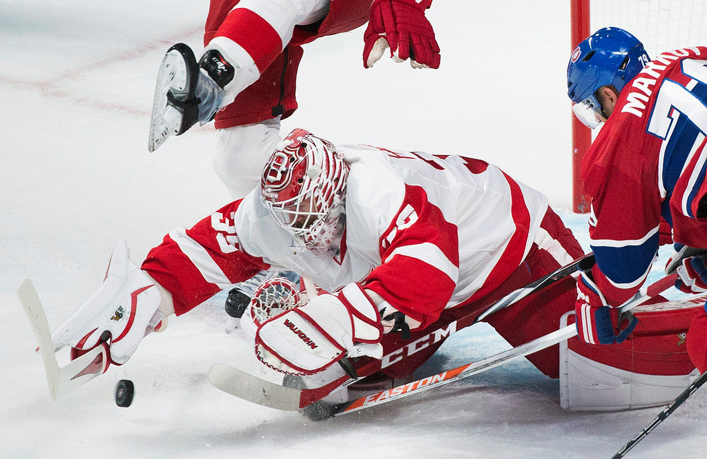 . Detroit Red Wings goaltender Jimmy Howard, left, makes a save against Montreal Canadiens\' Andrei Markov during second period NHL hockey action in Montreal, Tuesday, Oct. 21, 2014. (AP Photo/The Canadian Press, Graham Hughes)