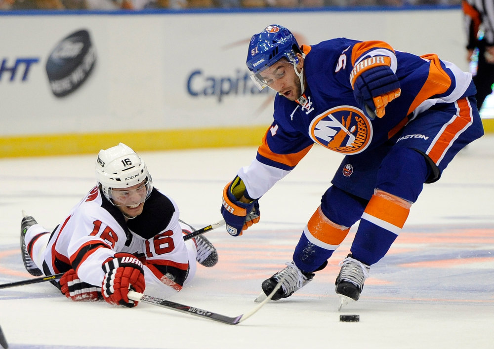 Description of . New Jersey Devils' Jacob Josefson (16) falls to the ice to drive the puck away from New York Islanders' Frans Nielsen (51) in the first period of an NHL hockey game on Saturday Jan., 19, 2013 at Nassau Coliseum  in Uniondale, N.Y. (AP Photo/Kathy Kmonicek)