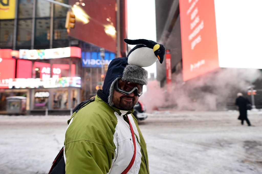 . A man wearing a hat with a penguin on it walks at the nearly deserted New York\'s Times Square what is normally a crowed morning rush hour after a snowstorm on January 27, 2015. A blizzard initially billed as possibly one of the worst ever in New York left only moderate snow in the Big Apple -- and officials and forecasters red-faced -- as New England bore the brunt of the storm on January 27. Travel bans were lifted and limited public transport resumed in New York, where officials were forced to launch a vigorous defense of the measures put in place as Winter Storm Juno moved in on Monday. AFP PHOTO/JEWEL SAMAD/AFP/Getty Images
