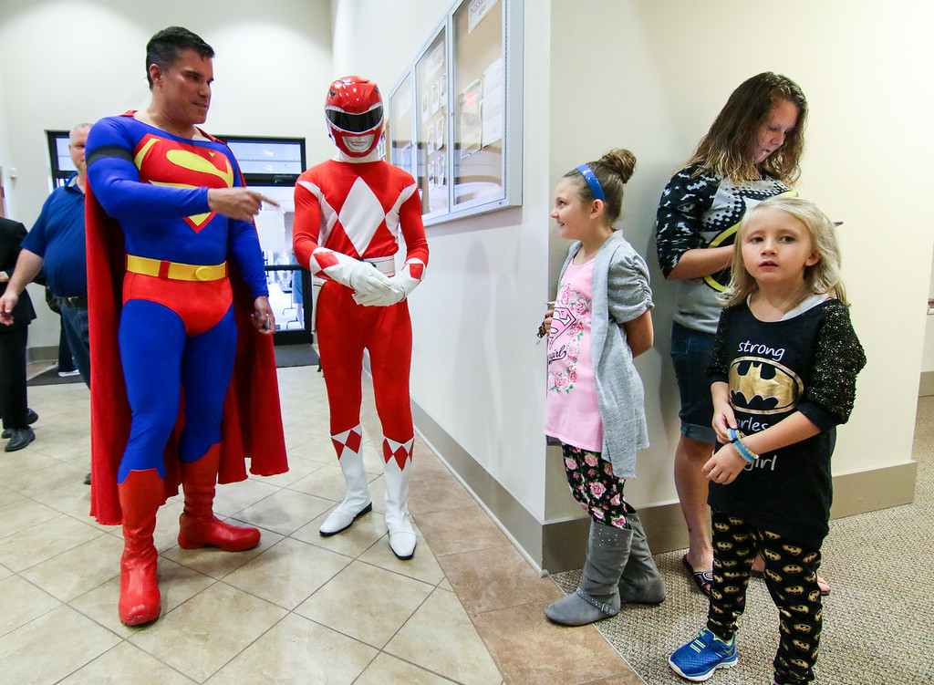 . Zowie Sanders, right, stands near John Suber, left, of Greenville, S.C. dressed as Superman, with her sister Lindsey Sanders, middle, and their mother Brooke Starks, right, during a wake service for Jacob Hall, at Oakdale Baptist Church, Tuesday, Oct. 4, 2016 in Townville, S.C. Townspeople and classmates filled a church Tuesday evening to say goodbye to Jacob Hall, a 6-year-old boy who died in a school shooting, filing past a casket adorned with large photos, balloons and a life-size figure of one of his favorite superheroes, Batman.(Ken Ruinard/The Independent-Mail via AP, Pool)
