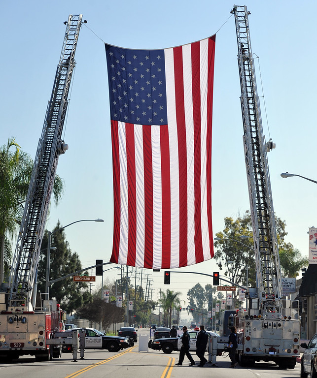 . Los Angeles County firefighters drape their flag at the entrance for the Grand Opening of the El Monte Veterans Village on Ramona Blvd. in El Monte on Wednesday March 12, 2014. The Veterans Village is a state-of-the-art veterans housing community includes 40 studio apartments. (Staff Photo by Keith Durflinger/San Gabriel Valley Tribune)