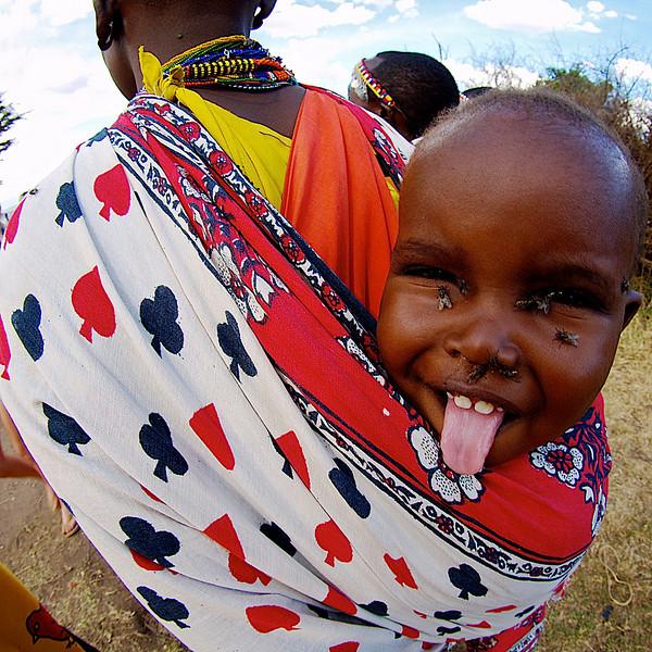 Fluefjes. Liten unge på ryggen til moren, Ololamutiek Gate, Masai Mara, Kenya oktober 2007. *** Fly me away. Small child on mother's back. Ololamutiek Gate, Masai Mara, Kenya October 2007. (Foto: Geir)