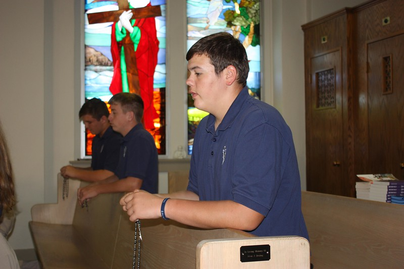 Conner Staab prays with members of the sophomore class in the TMP-Marian Chapel.