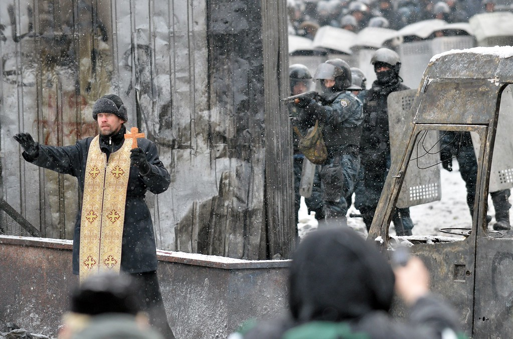 . An Orthodox priest tries to stop clash protesters the police in the center of Kiev on January 22, 2014. Ukrainian police on Wednesday stormed protesters\' barricades in Kiev as violent clashes erupted and activists said that one person had been shot dead by the security forces. Total of two activists shot dead during clashing. The move by police increased tensions to a new peak after two months of protests over President Viktor Yanukovych\'s failure to sign a deal for closer ties with the EU. SERGEI SUPINSKY/AFP/Getty Images