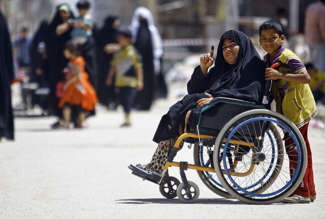 . An Iraqi woman in a wheelchair displays her ink-stained finger after voting in the central Shiite holy city of Najaf during the country\'s general elections on April 30, 2014. Iraqis streamed to voting centres nationwide, amid the worst bloodshed in years, as Prime Minister Nuri al-Maliki seeks reelection.  (HAIDER HAMDANI/AFP/Getty Images)