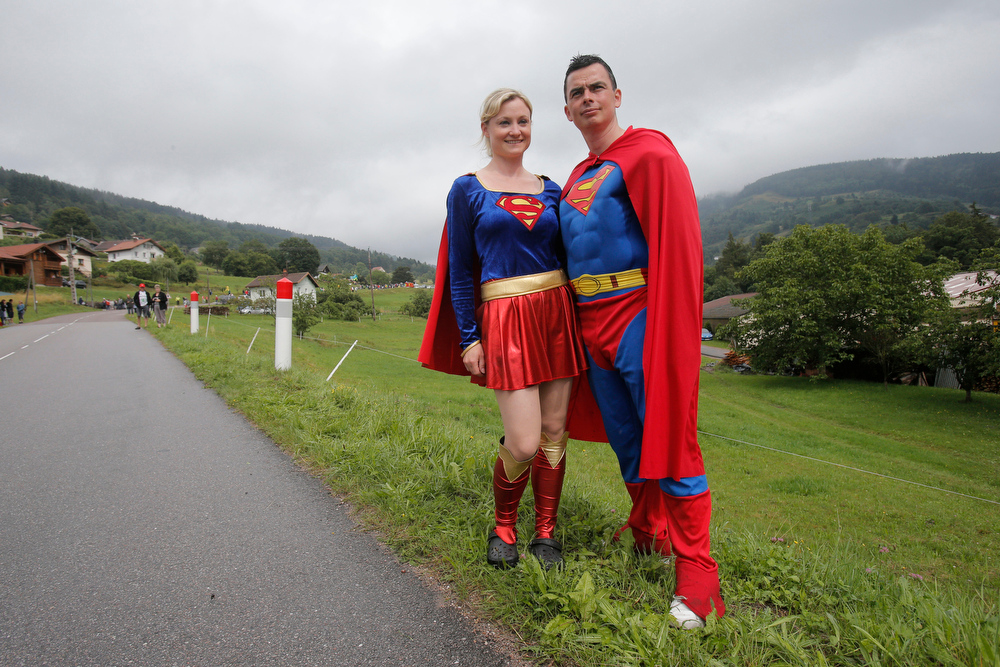 . Two people dressed as Superman and Superwoman wait for the riders to pass the eighth stage of the Tour de France cycling race over 161 kilometers (100 miles) with start in Tomblaine and finish in Gerardmer, France, Saturday, July 12, 2014. (AP Photo/Christophe Ena)