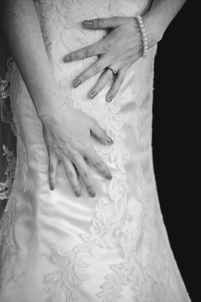 The bride's hands with pearl bracelet, black stoned wedding ring, and sparkly nails against her hip.