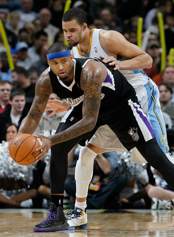 . Sacramento Kings center DeMarcus Cousins, front, looks to pass as Denver Nuggets center JaVale McGee defends in the third quarter of the Nuggets\' 121-93 victory in an NBA basketball game in Denver on Saturday, Jan. 26, 2013. (AP Photo/David Zalubowski)