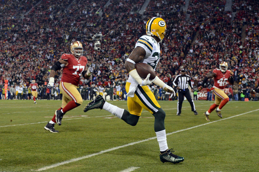 Description of . Cornerback Sam Shields #37 of the Green Bay Packers runs the ball back for touchdown after an interception against quarterback Colin Kaepernick #7 of the San Francisco 49ers in the first quarter during the NFC Divisional Playoff Game at Candlestick Park on January 12, 2013 in San Francisco, California.  (Photo by Harry How/Getty Images)