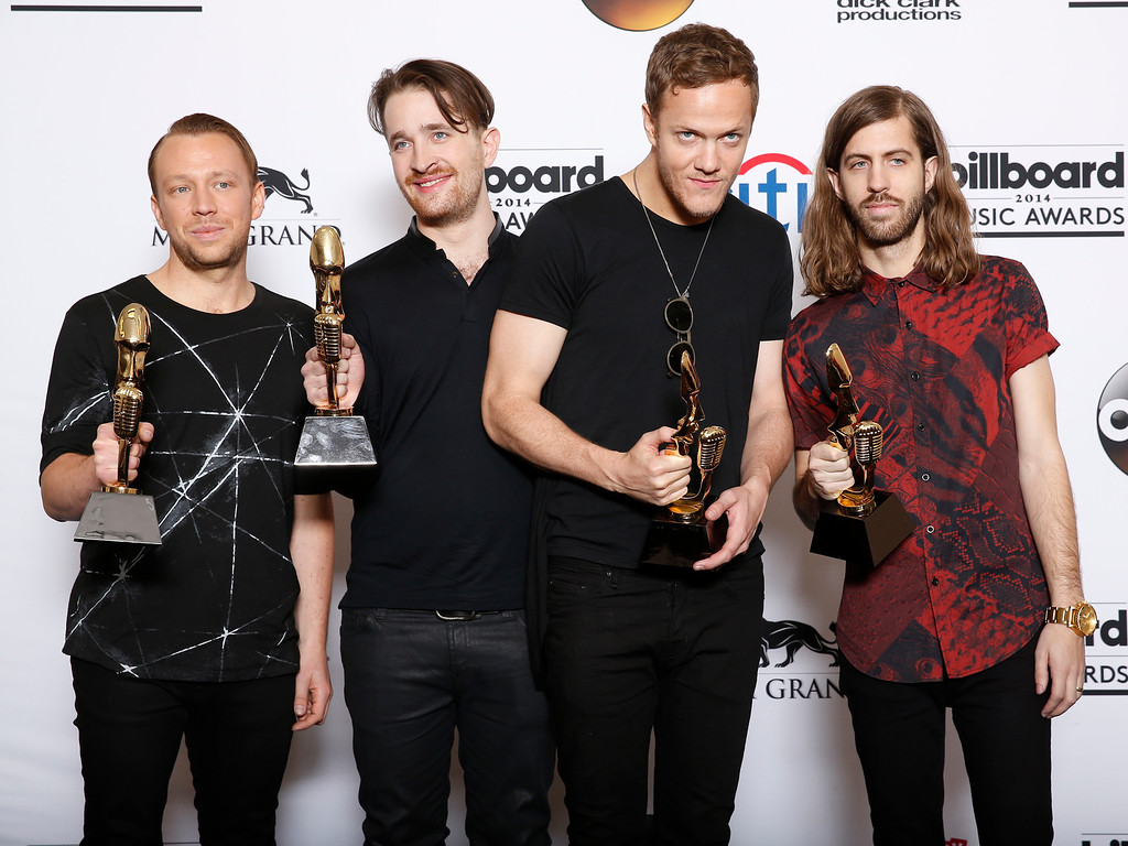 ". Ben McKee, from left, Daniel Platzman, Dan Reynolds and Wayne Sermon, of the musical group Imagine Dragons, poses in the press room with the award for top rock album for ""Night Visions\"" at the Billboard Music Awards at the MGM Grand Garden Arena on Sunday, May 18, 2014, in Las Vegas. (Photo by Eric Jamison/Invision/AP)"