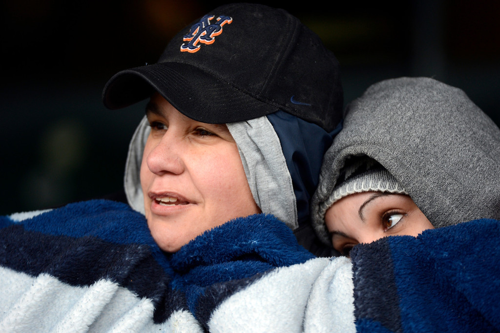 . Lisa Starcher ,44, and Angelica Colon, 28, keep warm under a blanket during the Colorado Rockies New York Mets game April 16, 2013 at Coors Field. (Photo By John Leyba/The Denver Post)