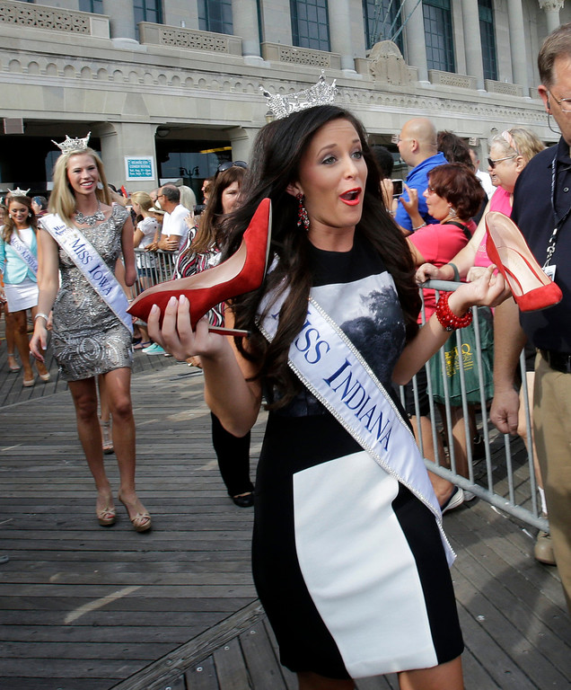 . Miss Indiana Terrin Thomas lost her shoes as Miss America contestants arrive in Atlantic City, Tuesday, Sept. 3, 2013. The Miss America pageant is back in the city where it began, six years after spurning the city for Las Vegas. The pageant held a welcoming ceremony Tuesday for the 53 contestants, one from each state plus the District of Columbia, Puerto Rico and the U.S. Virgin n Islands. The contestants filed out of Boardwalk Hall, where the competition will begin next week and culminate days later, and walked across the Boardwalk to a stage. (AP Photo/Mel Evans)