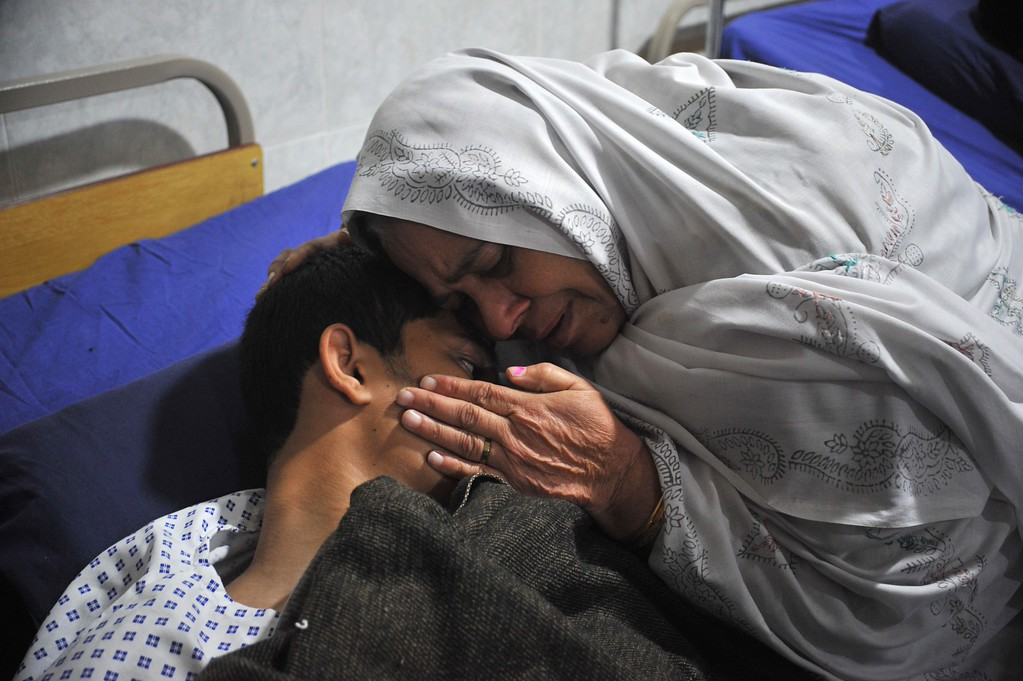 . A Pakistani mother reacts with her injured son a day after an attack on an army-run school by Taliban militants in Peshawar on December 17, 2014.  Pakistan began three days of mourning on December 17 for the 132 schoolchildren and nine staff killed by the Taliban in the country\'s deadliest ever terror attack as the world united in a chorus of revulsion.  AFP PHOTO / HASHAM  AHMED/AFP/Getty Images