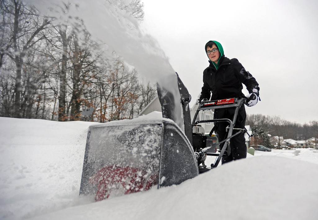 . Justin Bayly, 14, pushes a snow blower along Stoneledge Drive Wednesday, Feb. 5, 2014, in State College, Pa. Icy conditions Wednesday knocked out power to more than 560,000 electric customers in eastern and central Pennsylvania and prompted school closures, legislative delays and speed reductions on major roadways.  (AP Photo/Centre Daily Times, Nabil K. Mark)