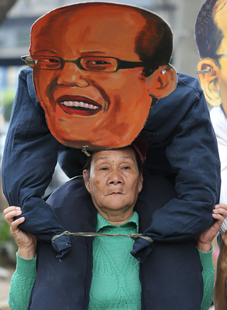 Description of . A woman activist carries an effigy of Philippine President Benigno Aquino III during a rally to mark International Women's Day in Manila, Philippines on Saturday, March 8, 2014. The group are blaming President Aquino who they alleged to have neglected women and their families. (AP Photo/Aaron Favila)