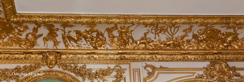 Inside the Chateu Versailles: hunting scenes in gold leaf on the ceiling moulding