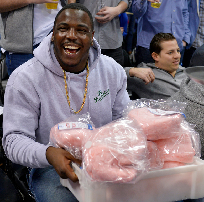 . Denver Broncos\' Malik Jackson jokes around with a box of cotton candy during the second quarter of an NBA basketball game between the Denver Nuggets and the Indiana Pacers Saturday, Jan. 25, 2014, in Denver. (AP Photo/Jack Dempsey)