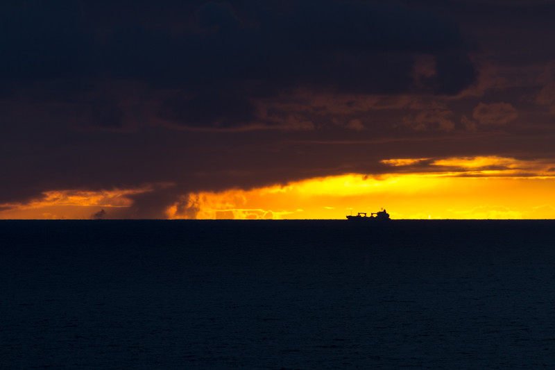 Golden sunset with a tinker ship silhouetted on the horizon