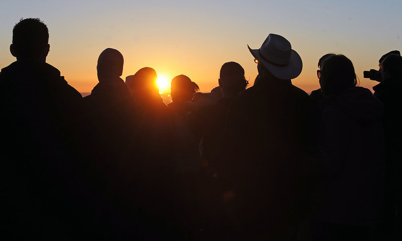 . People watch as the sun breaks the horizon as it rises in the east.  Thousands of people turned out for the sixty sixth annual Easter sunrise service at Red Rocks Amphitheatre in Golden on March 31st, 2013.The sun rose at 6:45 am under cloudless skies and this year\'s service was pleasant with warmer temperatures than in previous years.  The service, sponsored by the Colorado Council of Churches, was led by Reverend Dr. Jim Ryan and presided over by Reverend Dr. Janet Forbes.  (Photo By Helen H. Richardson/ The Denver Post)