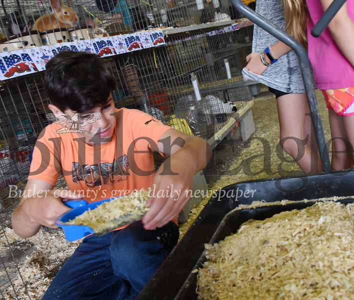 Harold Aughton/Butler Eagle: Will Scvhwalm,11, of Butler helps clean out the rabbit pens at the Butler Fair, Saturday, June 29.