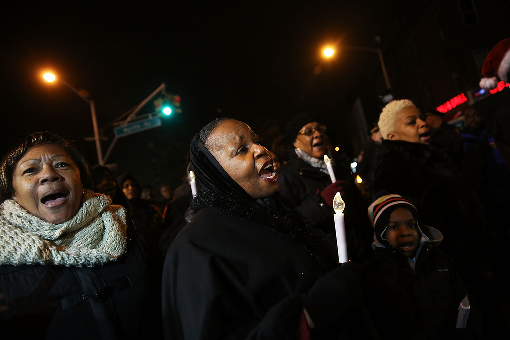 . NEW YORK, NY - DECEMBER 21:  Residents and area church members sing at a vigil for two New York City police officers at the location where they were killed, December 21, 2014 in New York City. The police officers were shot execution style Saturday afternoon as they sat in their marked police car on a Brooklyn street corner. The suspect, who allegedly shot his girlfriend in Baltimore earlier in the day, is believed to have been motivated by the deaths of Eric Garner and Michael Brown.  (Photo by Spencer Platt/Getty Images)