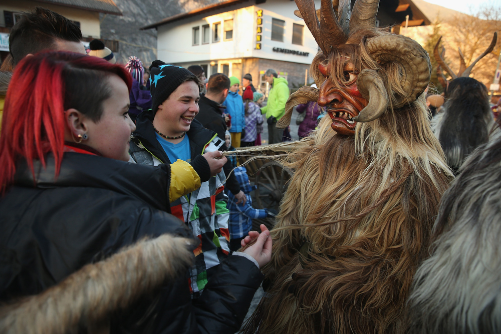 . A member of the Haiminger Krampusgruppe dressed as the Krampus creature lets himself be touched by onlookers prior to the annual Krampus night in Tyrol on December 1, 2013 in Haiming, Austria. Krampus, in Tyrol also called Tuifl, is a demon-like creature represented by a fearsome, hand-carved wooden mask with animal horns, a suit made from sheep or goat skin and large cow bells attached to the waist that the wearer rings by running or shaking his hips up and down. Krampus has been a part of Central European, alpine folklore going back at least a millennium, and since the 17th-century Krampus traditionally accompanies St. Nicholas and angels on the evening of December 5 to visit households to reward children that have been good while reprimanding those who have not. However, in the last few decades Tyrol in particular has seen the founding of numerous village Krampus associations with up to 100 members each and who parade without St. Nicholas at Krampus events throughout November and early December.  (Photo by Sean Gallup/Getty Images)