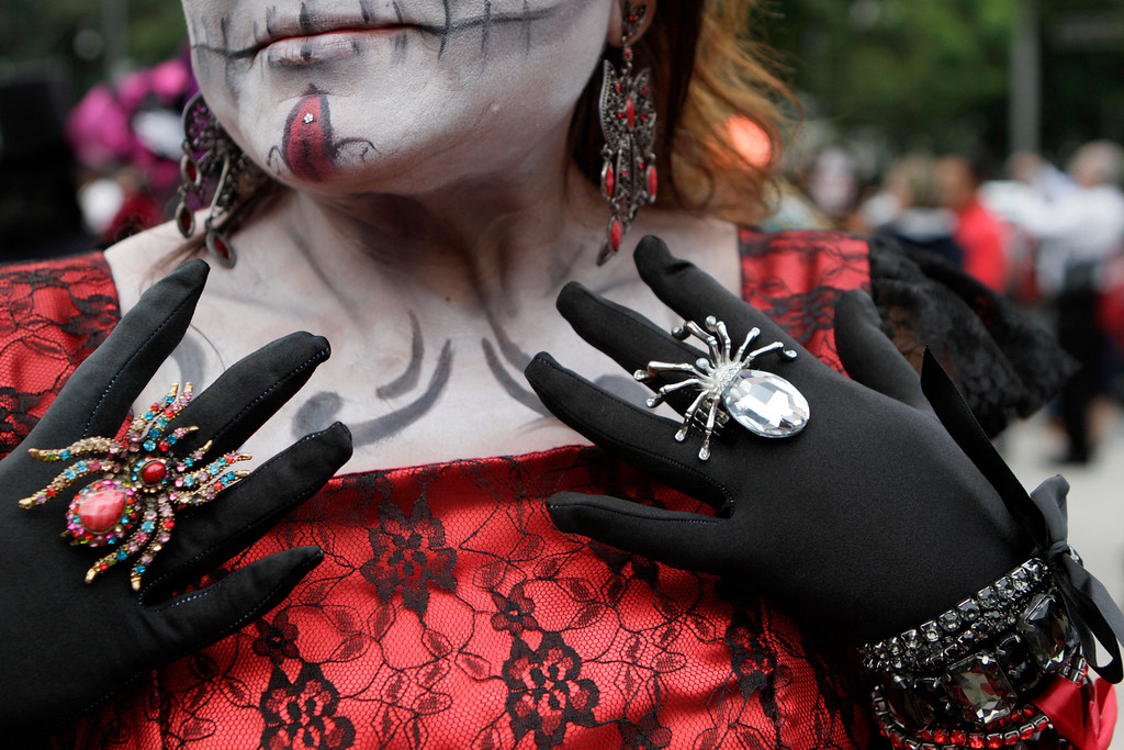 ". Ruby Valdez, dressed as a ""Catrina,\"" or skeleton lady, waits for the start of the Gran Procession of the Catrinas, to mark the upcoming Day of the Dead holiday, in Mexico City, Sunday, Oct. 23 2016. The gran procession is one of many that will take place in Mexico City as part of the celebrations, culminating with visits to the graves of departed loved ones on Nov. 1 and 2. The figure of a skeleton wearing broad-brimmed hat was first done as a satirical engraving by artist Jose Guadalupe Posada sometime between 1910 and his death in 1913, to poke fun at women who pretended to be European by dressing elegantly and as a critique of social stratification. (AP Photo/Anita Baca)"