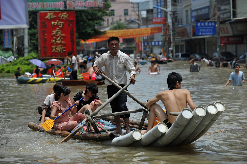 . Flood victims making their way down a flooded street in Shantou, in southern China\'s Guangdong province.  Devastating floods at opposite ends of China have left 105 people dead and another 115 missing in recent days, state media said on August 19.   AFP PHOTOSTR/AFP/Getty Images