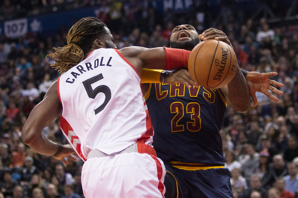 . Cleveland Cavaliers forward LeBron James, right, is fouled by Toronto Raptors forward DeMarre Carroll during the second half of an NBA basketball game in Toronto on Friday, Oct. 28, 2016. (Chris Young/The Canadian Press via AP)