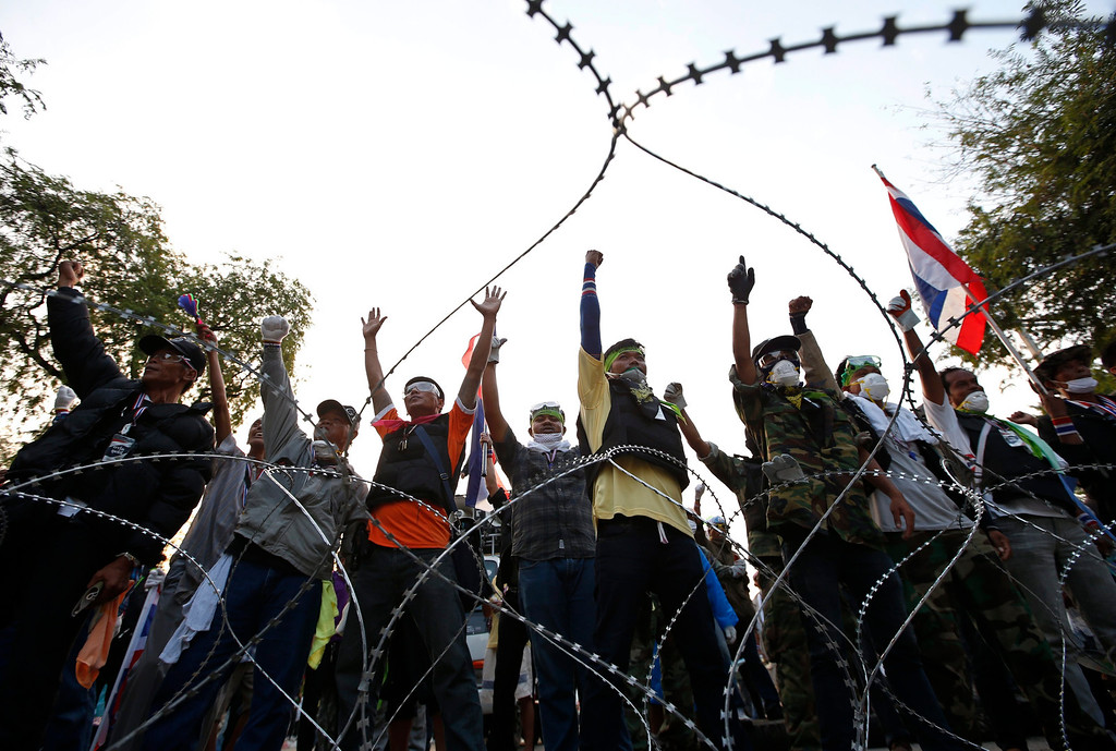 . Thai anti-government protesters shout slogans behind barbed wire at a protest site near Government House in Bangkok, Thailand, 18 February 2014.  EPA/RUNGROJ YONGRIT