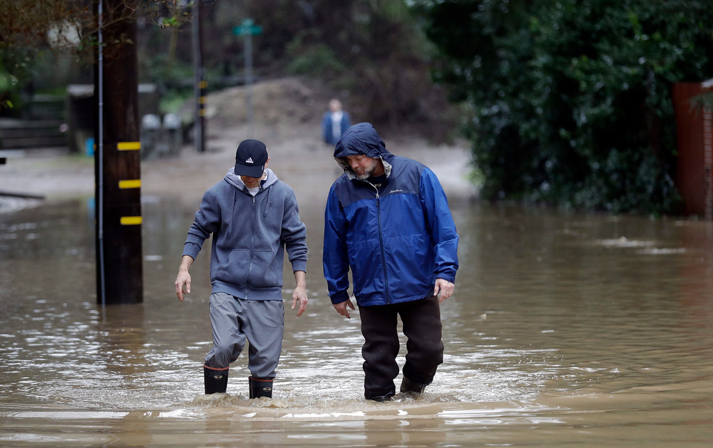 . Two men walk alongside a flooded street Tuesday, Feb. 7, 2017, in Felton, Calif. Flash flood watches are in place for parts of Northern California down through the Central Coast as heavy rains swamp roads and threaten to overtop rivers and creeks. (AP Photo/Marcio Jose Sanchez)