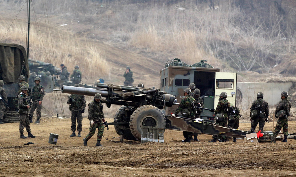 """. South Korean soldiers prepare to fire 155 mm howitzers during their military exercise in the border city between two Koreas, Paju, north of Seoul, South Korea, Friday, April 5, 2013. After a series of escalating threats, North Korea has moved a missile with \""""considerable range\"""" to its east coast, South Korea\'s defense minister said Thursday. But he emphasized that the missile was not capable of reaching the United States and that there are no signs that the North is preparing for a full-scale conflict. (AP Photo/Lee Jin-man)"""