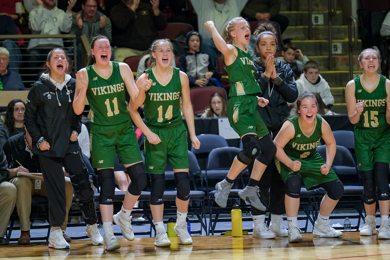 The Oxford Hills' bench celebrates a late foul shot by Cassidy Dumont.
