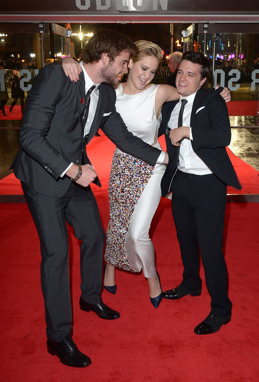 . Actors Liam Hemsworth, left, Jennifer Lawrence and Josh Hutcherson share a joke on the red carpet as they arrive for the World Premiere of \'The Hunger Games: Catching Fire\', on Monday Nov. 11, 2013, in Leicester Square, London. \'Catching Fire\' is the second installment in \'The Hunger Games\' trilogy. (Photo by Jon Furniss/Invision/AP)