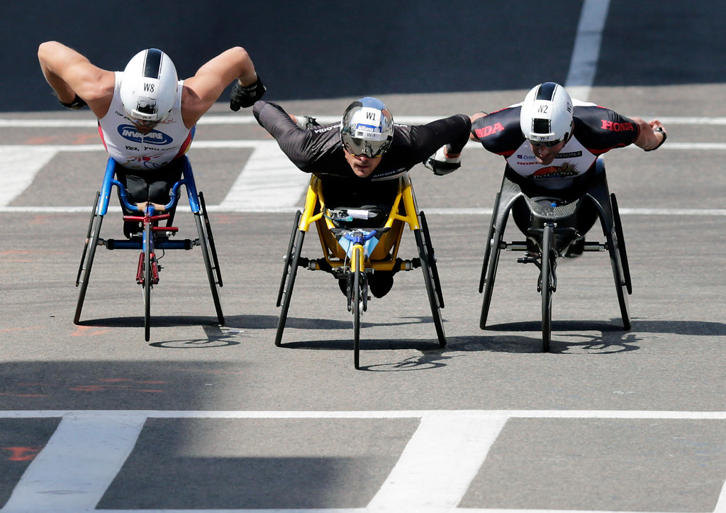 . Marcel Hug, of Switzerland, center, inches ahead of Kurt Fearnley, of Australia, left, and Ernst Van Dyk, of South Africa on his way to winning the wheelchair division of the 120th Boston Marathon on Monday, April 18, 2016, in Boston. (AP Photo/Charles Krupa)