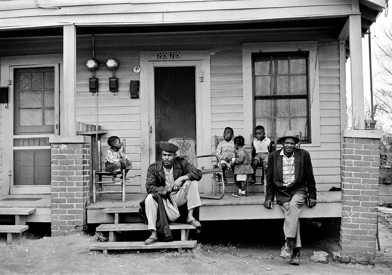 MONTGOMERY, AL - MARCH 25:  African-American children  seated on rear of porch of home, with two men sitting on edge of porch, while watching Selma to Montgomery, Alabama marchers passing by in front of home.