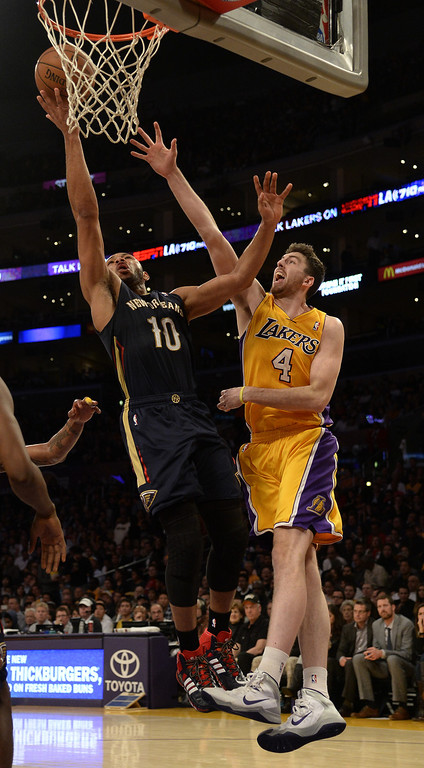 . New Orleans Pelicans shooting guard Eric Gordon (L) goes up for a shot as he is defended by Los Angeles Lakers power forward Ryan Kelly (R) during the second half of their NBA game at the Staples Center in Los Angeles, California, USA, 04 March 2014.  The Pelicans won the game.  EPA/MICHAEL NELSON