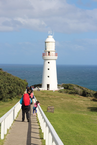 Visitors troop down a paved path bordered by a white fence on their way to the white lighthouse overlooking the ocean.