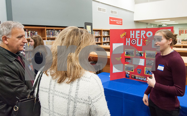 12/12/17 Wesley Bunnell | Staff The Berlin Upbeat Club held their 2017-18 Senior Expo on Tuesday evening at the high school. The expo featured Upbeat House Leaders discussing the focus of each house's activities. Sarah Giuliano from Hero House explains the house's activities to visitors.