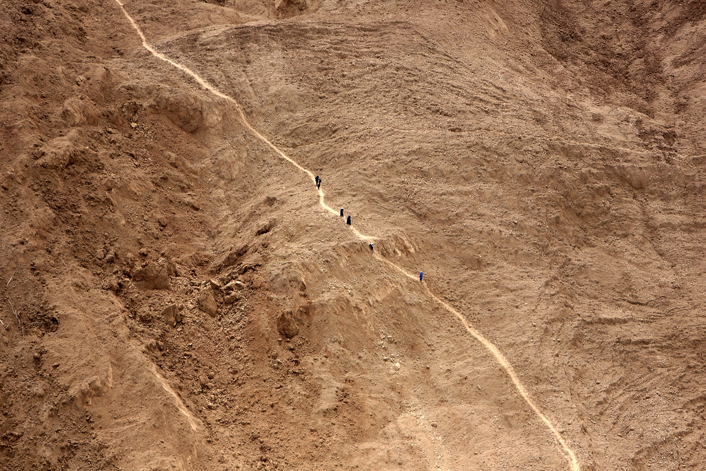 . An aerial view shows people walking near the site of Friday\'s landslide that buried Abi Barik village in Badakhshan province, northeastern Afghanistan, Monday, May 5, 2014.  (AP Photo/Rahmat Gul)