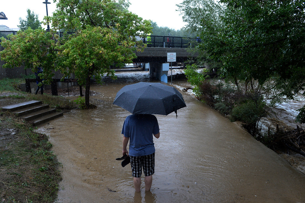 . BOULDER, CO. - SEPTEMBER12:  A man looks over the flooded bike path along Boulder Creek in Boulder CO September 12, 2013. Record-breaking rain turned normally quiet creeks into raging, brown torrents that swept through Boulder on Thursday, flooding homes, swamping cars and closing roads and schools. (Photo By Craig F. Walker / The Denver Post)