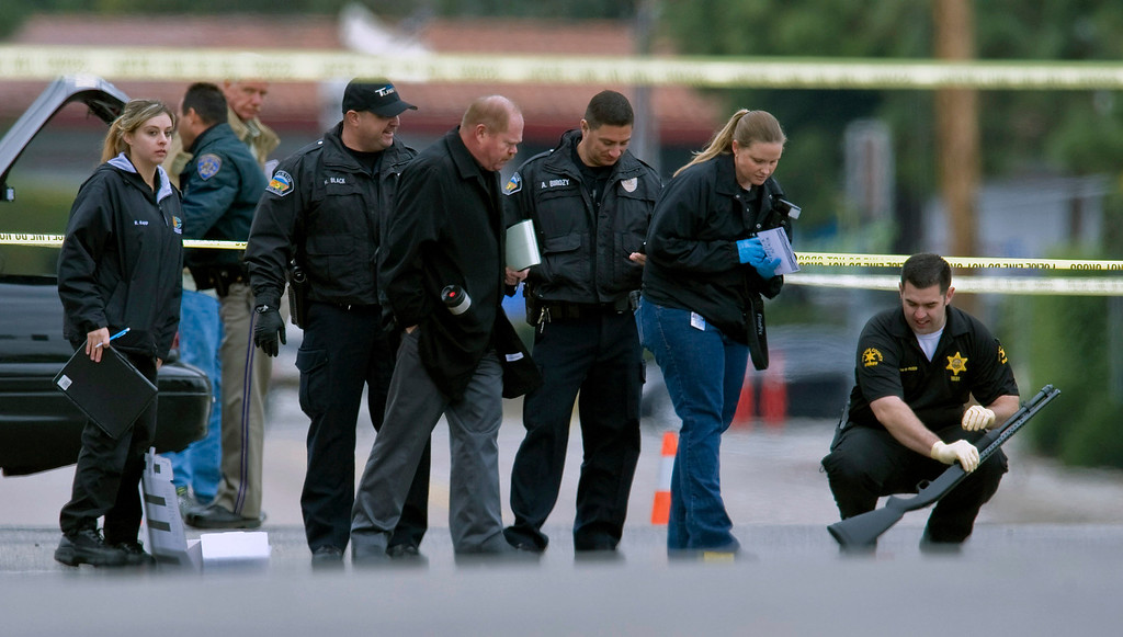 . Police investigators examine a gun laying in the street at the intersection of Wanda Road and Katella Avenue in Orange, Calif., Tuesday, Feb. 19, 2013.  (AP Photo/The Orange County Register, Mark Rightmire)