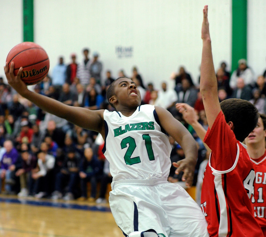 . Blazers guard Reginald Gibson (21) lobbed  a shot over Regis defender Kip Borya (44) in the second half. The Overland High School boy\'s basketball team defeated Regis Jesuit 80-66 Tuesday night, December 11, 2012.  Karl Gehring/The Denver Post