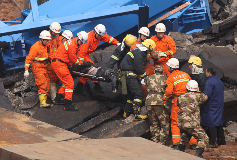 Description of . Rescuers carry a dead body (C) at the scene of the collapsed Yichang bridge near the city of Sanmenxia, central China's Henan province, on February 1, 2013 after a fireworks-laden truck exploded as it crossed the bridge killing 26 people as the structure collapsed and vehicles plummeted to the ground, state-run media reported. An 80-meter long part of the bridge collapsed and six vehicles had been retrieved from the debris, China's official news agency Xinhua said. The bridge near the city of Sanmenxia is on the G30 expressway, the longest road in China, which stretches for nearly 4,400 kilometers (2,700 miles) from China's western border with Kazakhstan to the eastern Yellow Sea. AFP PHOTO STR/AFP/Getty Images