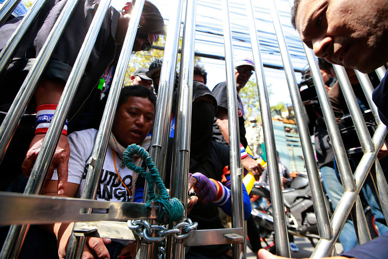 . Thai anti-government protesters use chain to lock up the gate at the fishery department as they close down the office Tuesday, Jan. 21, 2014 in Bangkok, Thailand. Twin explosions shook an anti-government demonstration site in Thailand\'s capital, wounding more than dozens of people in the latest violence to hit Bangkok as the nation\'s increasingly bloody political crisis drags on. (AP Photo/Wason Wanichakorn)