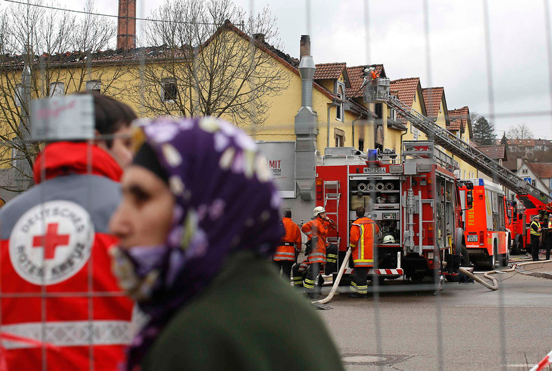 . A women and a red cross member stand in front of the scene of a fire in Backnang, Germany on March 10, 2013. At least eight people, including seven children, died after a fire broke out in a building in the southern German province of Baden-Wuerttemberg. The cause of the fire is not yet known. REUTERS/Lisi Niesner