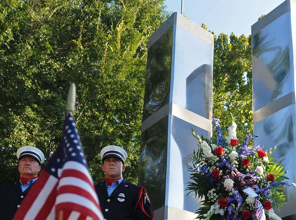 . Hattiesburg firefighters stand aside a memorial during the 9/11 Observance of Patriots\' Day ceremony in Hattiesburg Miss., Sept. 11, 2013.    (AP Photo/Hattiesburg American, Ryan Moore)